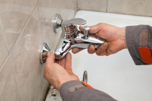 Plumber hands fixing water tap in a bathroom